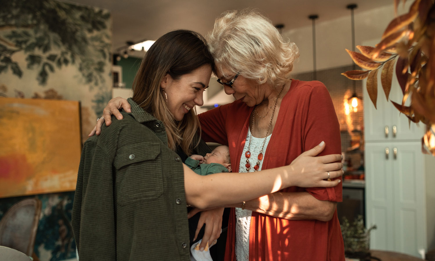 Three generations, with a grandma, new mom and baby, embracing in a hug